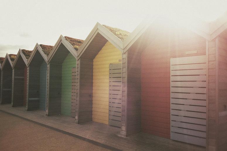 A row of colourful beach huts.